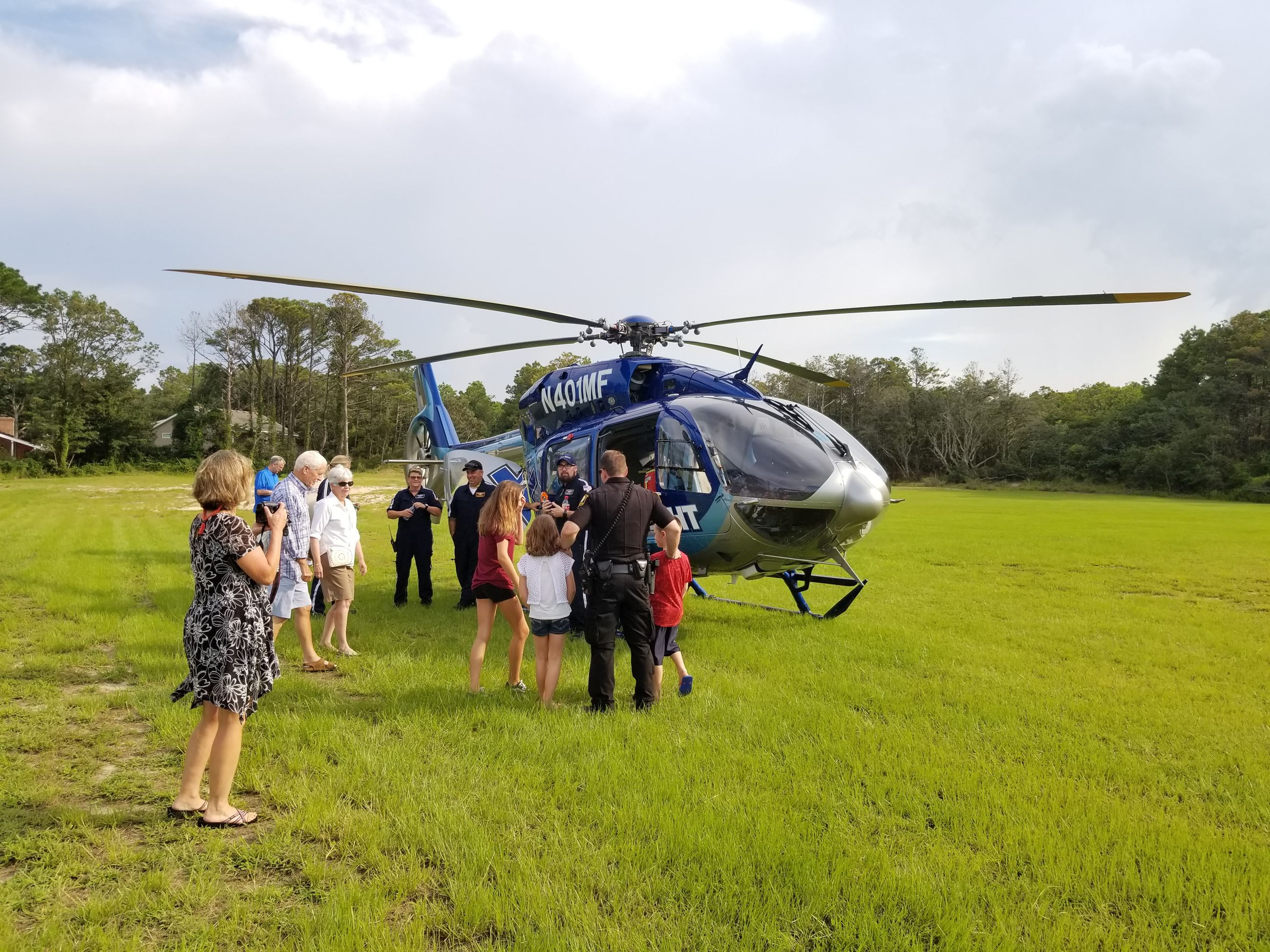 Landed helicopter with people gathered around
