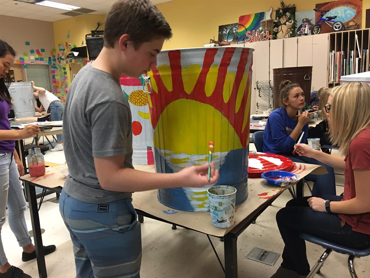 Young Man Painting Trashcan With Other Students